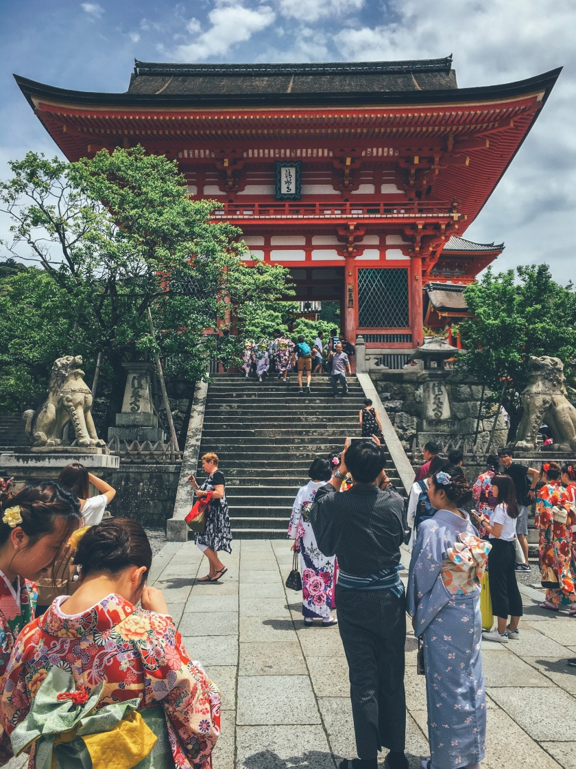 Shrine in Japan near Kyoto. People taking photos with iPhone wearing traditional Japanese garment.
