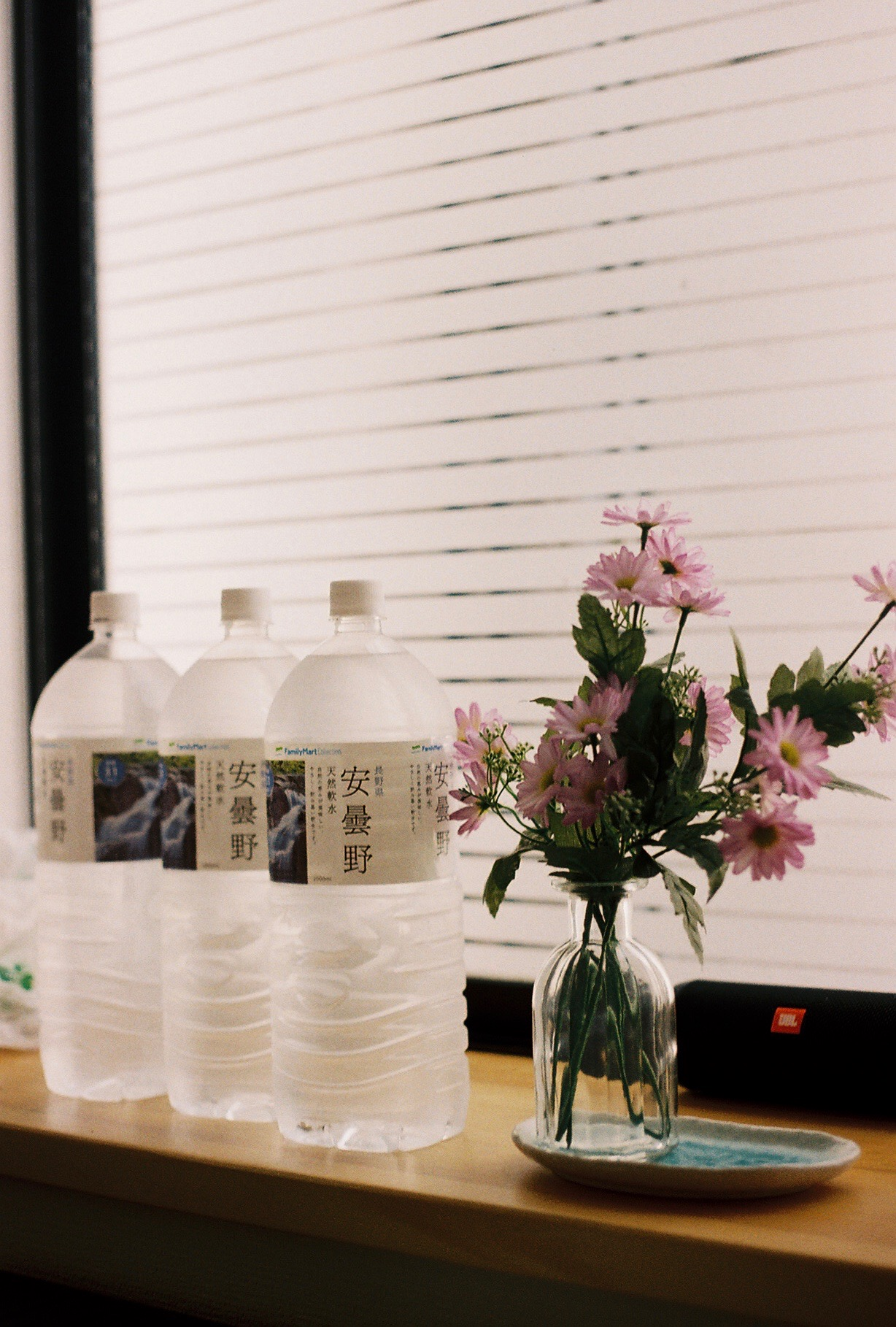 35mm photo of pink flowers in a glass vase placed next to three water bottles in the foreground with Japanese phrases written on them.