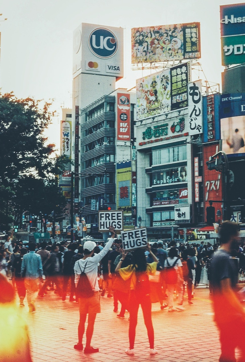 """35mm film photo in Shibuya crossing in Tokyo Japan its street photo of two people holding up signs that read """"free hugs"""" with a large crowd walking around them"""
